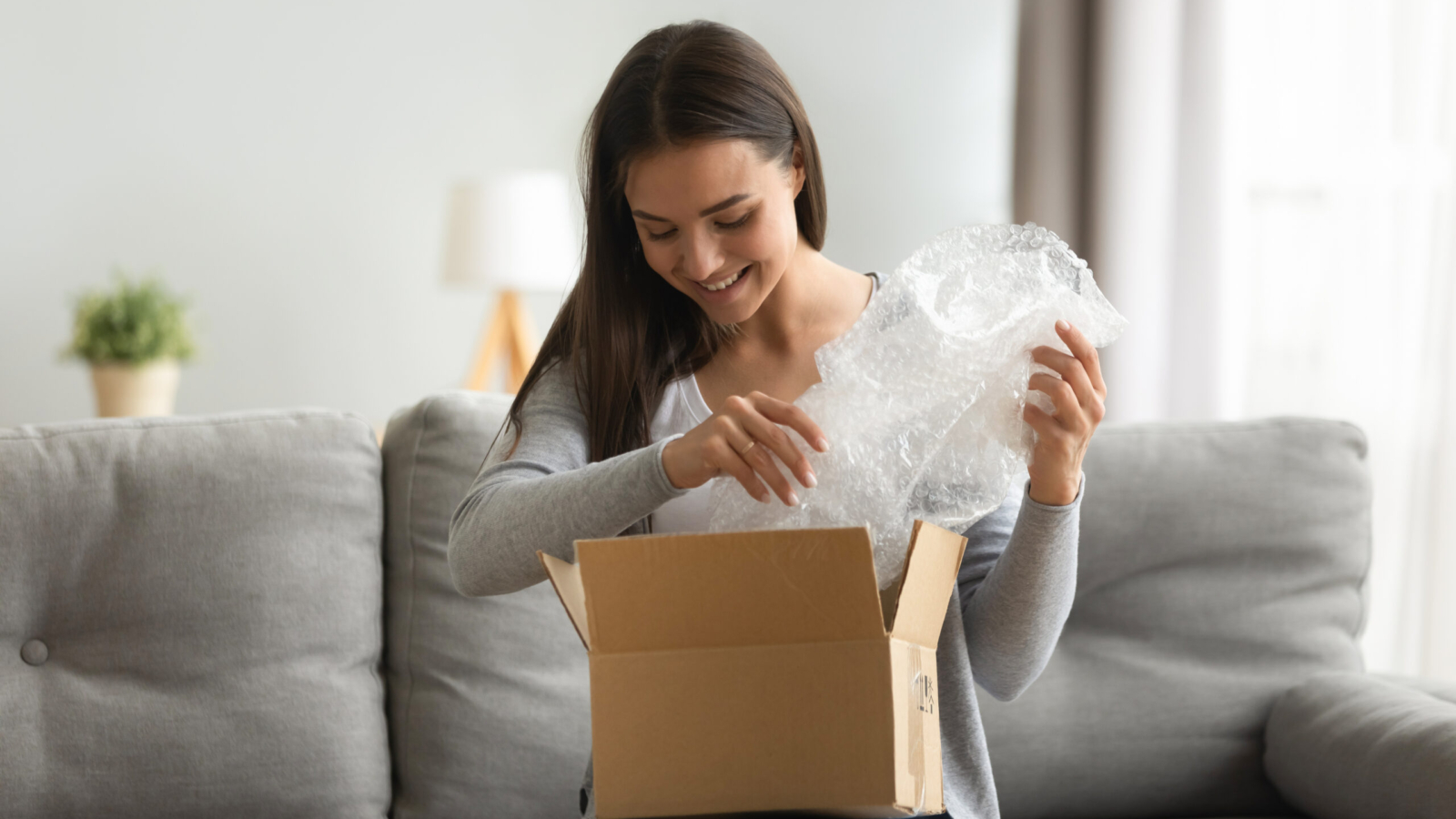 Happy young woman open cardboard box satisfied with purchase online shop order sit on sofa at home, smiling lady customer receive unpack parcel look inside, postal shipping courier service concept